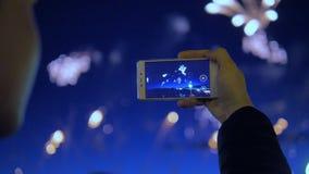 Mannen antecknar en video av fyrverkerier med hans telefon stock video
