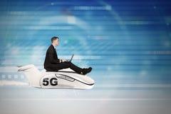 Mannen använder bärbara datorn på nivån med symbol för nätverk 5G royaltyfri fotografi