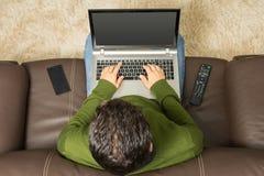 Mannen använder bärbara datorn på soffan Över huvudet sikt, brun soffa arkivbilder
