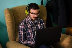 Mannen använder bärbara datorn på soffan i hans hem royaltyfri foto