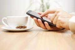 Mannen använder den smarta telefonen för mobilen nära koppen kaffe Royaltyfri Foto