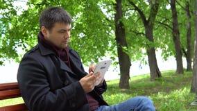 Mannen använder en minnestavla i parkera stock video