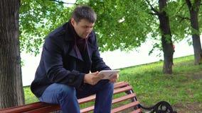 Mannen använder en minnestavla i parkera arkivfilmer