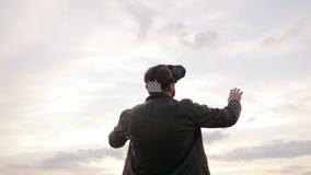 Mannen använder exponeringsglas för en virtuell verklighet mot himlen stock video