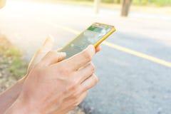 Mannen använder hans utomhus- mobiltelefon Royaltyfri Foto