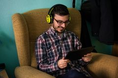 Mannen använder minnestavlan på soffan i hans hem royaltyfria bilder
