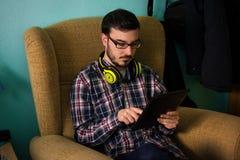 Mannen använder minnestavlan på soffan i hans hem arkivfoton