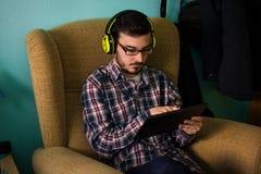 Mannen använder minnestavlan på soffan i hans hem royaltyfri foto