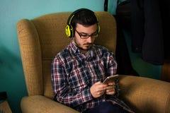 Mannen använder mobilen på soffan i hans hem arkivbilder