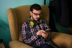 Mannen använder mobilen på soffan i hans hem royaltyfri fotografi
