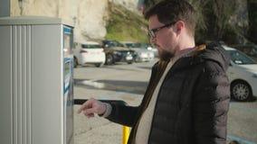 Mannen använder parkeringsmetern som trycker på knappar lager videofilmer