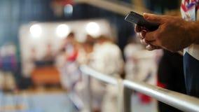 Mannen använder smartphonen på sportkonkurrenser av karate lager videofilmer