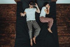 Mannen använder VR och kvinnan som sover på säng arkivbild