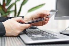Mannen använder kreditkorten och mobiltelefonen för på linjen betalning Royaltyfria Bilder