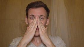 Mannen applicerar kräm på hans framsida applicera genomskinlig fernissa för omsorgshud stock video