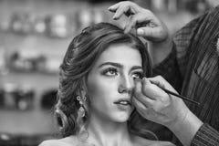 Mannen applicerar mascara på ögonfrornas härligt makeupkvinnabarn Arkivfoto