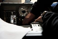 Mannen arbetar och reparerar datoren Arkivfoton