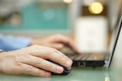 Mannen arbetar på bärbara datorn hemma Grunt djup av fältet, fokus Arkivbild