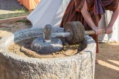 Mannen arbetar på forntida romersk press för olivolja Arkivfoton