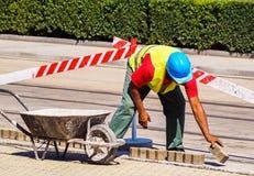 Mannen arbetar på vägkonstruktionen Arkivbild