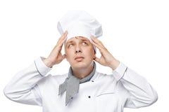 Mannen arbetar som en kock, korrigerar huvudbonaden på en vit royaltyfri bild