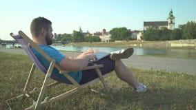 Mannen avslutar maskinskrivning på bärbara datorn och att kyla ut på sunbed av floden lager videofilmer