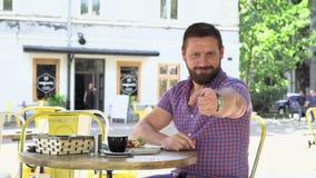 Mannen avslutar påringning, och punkter fingrar på kameran under frukosten lager videofilmer