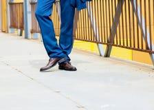 Mannen bär blå byxa med bruna skor royaltyfria bilder