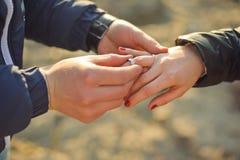 Mannen bär en vigselring på kvinnans hand Arkivfoton