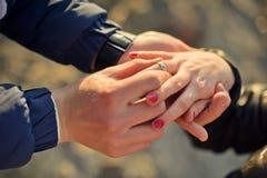 Mannen bär en vigselring på kvinnans hand Royaltyfria Foton