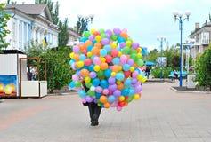 Mannen bär många ljusa ballonger Arkivfoton