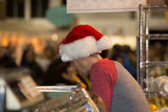 Mannen bär Santa Cap på marknaden Arkivfoton