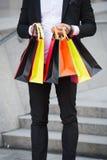 Mannen bär stads- bakgrund för shoppingpåsar Lyckad affärsman som direktanslutet shoppar Det upptagna folket uppskattar direktans arkivbild