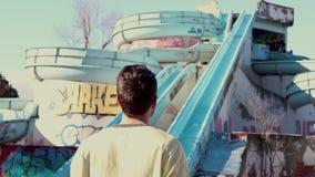 Mannen bakifrån av ett övergett vatten parkerar framme stock video