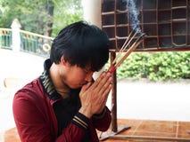 Mannen ber för buddha med josspinnen Arkivbild
