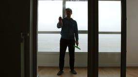 Mannen besprutar fönsterrengöringsmedlet på stort fönster och tvättar det i dagen - Front View stock video