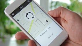 Mannen beställer taxien och accepterar höga frekvenser för ritten genom att använda smartphoneapplikation arkivfilmer