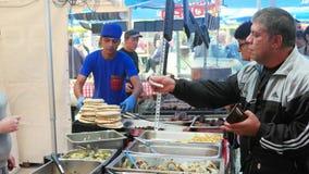 Mannen betalar kassa på matfestival, den öppna plånboken, gatamatfestivalen, man får pengar från handväskan stock video