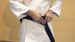 Mannen binder ett svart bälte på en vit kimono lager videofilmer