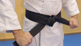 Mannen binder ett svart bälte på en vit kimono arkivfilmer