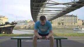 Mannen bläddrar översikten som sitter på bänk mot floden stock video