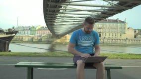 Mannen bläddrar bärbara datorn som sitter på bänk mot floden, steadicam lager videofilmer