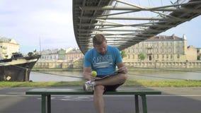 Mannen bläddrar magizne som äter ett äpple lager videofilmer