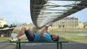 Mannen bläddrar minnestavlan som ligger på bänken mot floden arkivfilmer