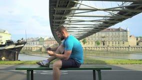 Mannen bläddrar minnestavlan som sitter på bänk mot floden lager videofilmer