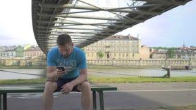 Mannen bläddrar smartphonen som sitter på bänk mot floden, pannaskottet arkivfilmer