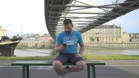 Mannen bläddrar smartphonen som sitter på bänk mot floden, pannaskottet stock video