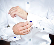 Mannen bär manschettknappar på en skjortamuff En brudgum som sätter på manschettknappar, som han får iklädda formella kläder dräk Arkivbilder