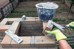 Mannen bygger en tegelstenugn arkivbilder