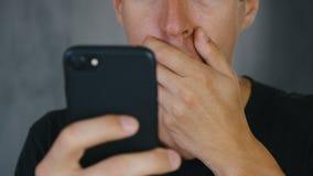 Mannen chockades av det dåliga meddelandet som han läste på hans smartphone Chockad och bedövad man för närbild lager videofilmer